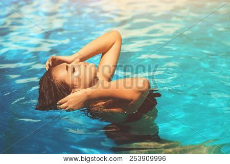 Fashion Photo Of Sexy Beautiful Girl With Brunette Hair In Elegant Bikini Sunbath In Swimming Pool.