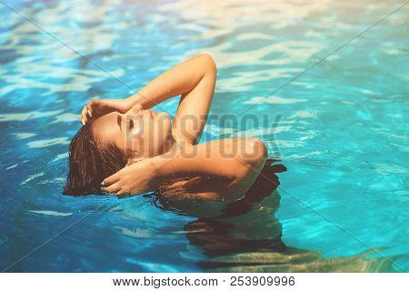 Sexy woman in black bikini in swimming pool. Beautiful woman wearing swimsuit. Closeup of woman's body in sexy bikini. Torso of luxurious woman. Big tits, biggest boobs, sexy breast, sexuality bra.Hot poster