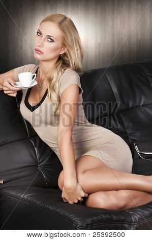 Sitting On Sofa Drinking From A Cup, She Look In To The Lens. She Look In To The Lens, Her Arms Are