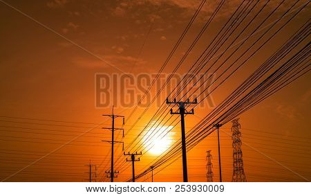 High Voltage Electric Pole And Transmission Lines At Sunset Time With Orange And Red Sky And Clouds.