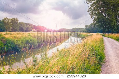 A Nice Non-urban Scene With The Demer River, A Towpath, Grass And Some Trees Under A Cloudy Sky With