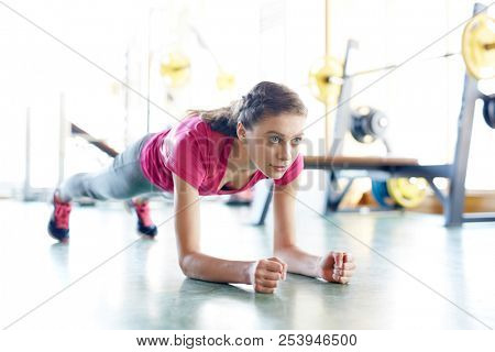 Young fit woman training in gym and doing plank exercise looking forward with determination