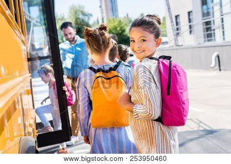 Little Schoolgirl Entering School Bus With Classmates While Teacher Standing Near Door
