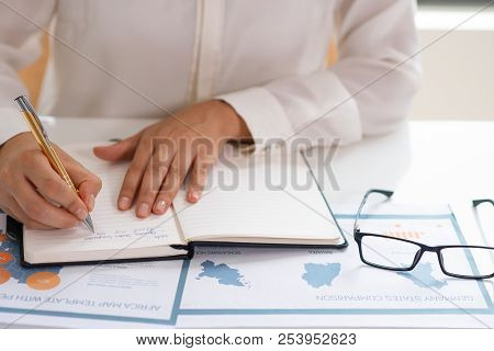 Business Leader Making Draft Of Business Plan. Female Manager Sitting At Table With Paper Graphs And