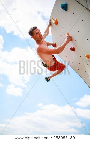 Photo of athlete looking at camera practicing on wall for rock climbing against blue sky with clouds