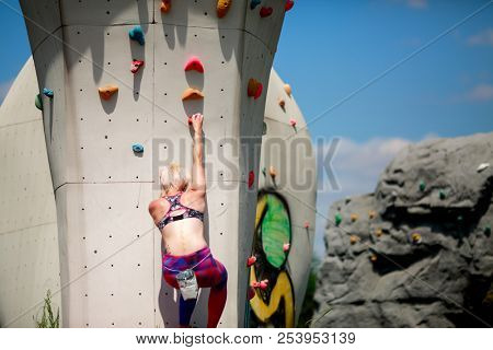 Photo from back of sports woman in leggings on wall for rock climbing against blue sky