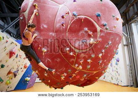 Photo from side of young athlete girl on red climbing ball in sports hall