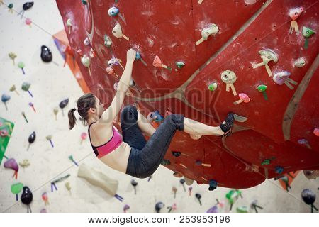 Photo of sports woman on red rock climbing ball in sports hall