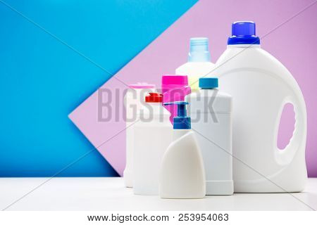Photo of bottles of cleaning products on white table isolated on blue , purple background