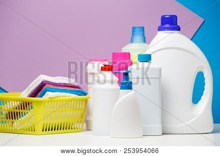 Photo of bottles of detergents and multi-colored towels in basket isolated on purple, blue background