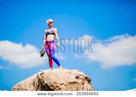 Photo of smiling woman climber with hands up on top of stone