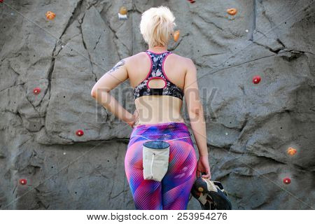 Photo from back of sports woman about climbing wall