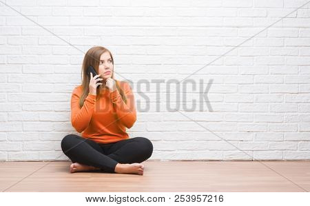 Young adult woman sitting on the floor over white brick wall calling using smartphone serious face thinking about question, very confused idea