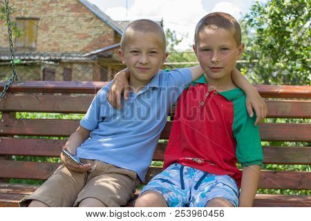 Two Boys Sitting On The Bench, Two Brothers Hugged Sitting On The Bench