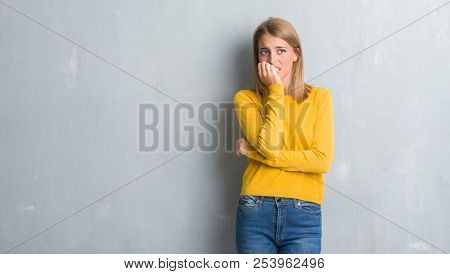 Beautiful young woman standing over grunge grey wall looking stressed and nervous with hands on mouth biting nails. Anxiety problem.