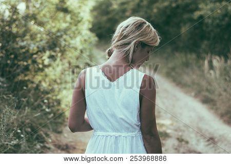 Solitude woman walking on dirt road poster
