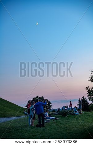 Munich,germany-august 15,2018: Some People Appear Blurred While Taking Pictures Of The Setting Sun F