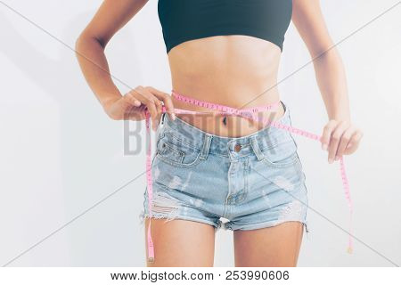 Slim Woman Measures Her Waist With Measuring Tape.