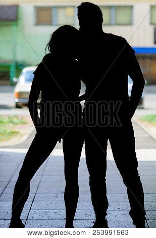 Silhouette Couple In Love Against Urban Background. Man And Slim Girl Posing In Shadow. Youth Meet F