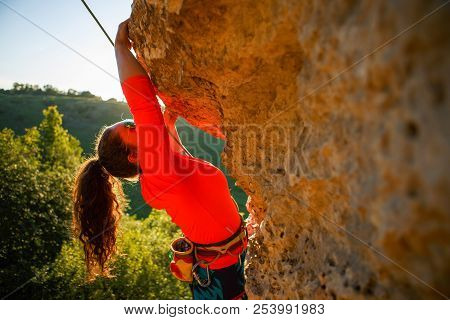Photo Of Curly-haired Female Tourist Clambering Over Rock On Summer Day
