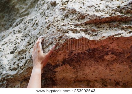 Picture Of Man's Hand Clambering Over Rock