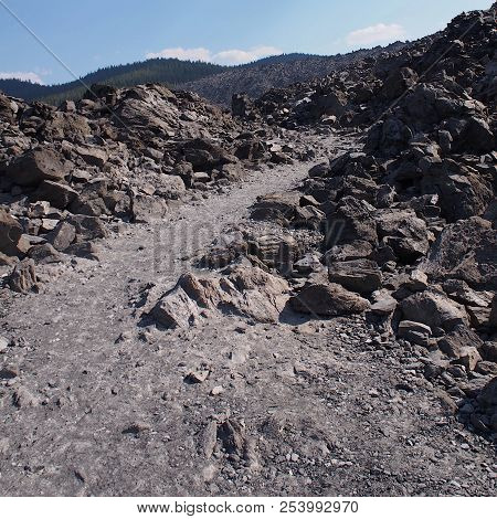 A Path Runs Through The  Rugged Terrain Of The Jagged Rocks At The Big Obsidian Flow In The Newberry