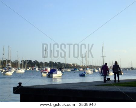 Couple Strolling Along Boat Marina/