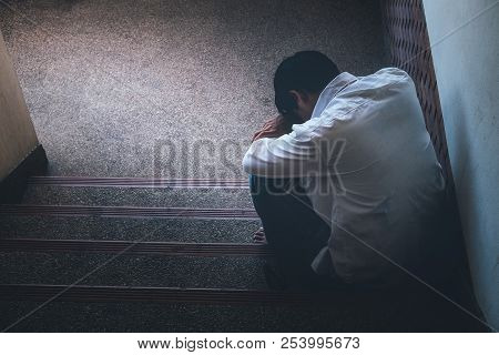 Depressed Man Sitting Head In Hands On The Stairs In Building. With Low Light Environment, Dramatic