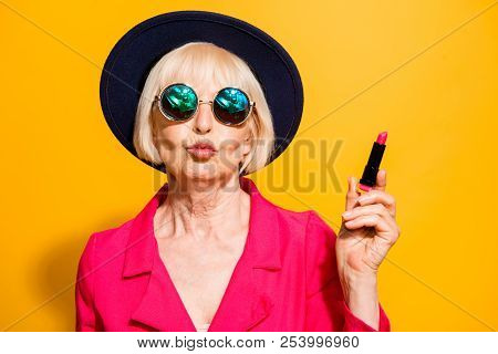 Grandmother getting ready for date! Charming, attractive old woman holding red lipstick pouting lips for a kiss isolated on brigth yellow background poster