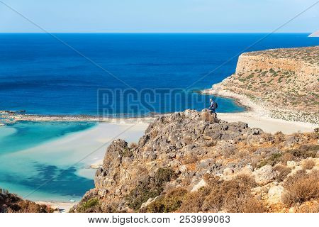 Traveler With A Backpack Stands On A Rock And Looks At The Panorama Of The Balos Beach, Crete, Greec