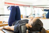 Full length of body conscious woman exercising on pilates reformer machine in gym poster