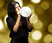 portrait of young woman blowing balloon against a abstract lights background poster
