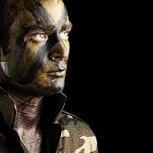 portrait of young soldier face with jungle camouflage against a black background poster
