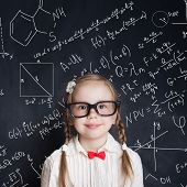 Little genius. Smart little girl math student on school blackboard background with hand drawings science formula pattern. Kids mathematics education concept poster