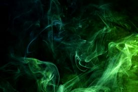 Cloud Of Blue And Green Smoke On A Black Isolated Background. Background From The Smoke Of Vape