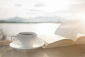 Cup Of Coffee And Book On A Wooden Table In Morning Sunlight With A Natural Background