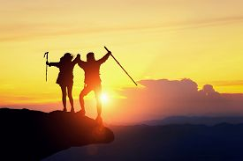 Silhouette Of Backpacker Hiking On Sunset Mountain Peak