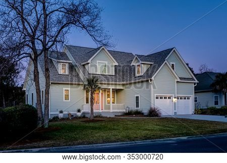 offset view of beautiful luxury home at dusk with lights.