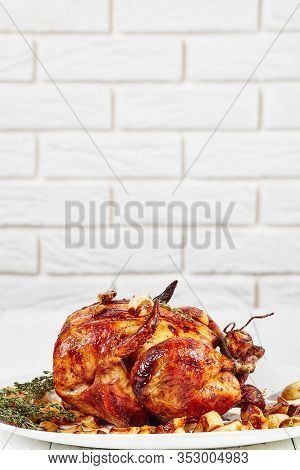 Roast Chicken With Forty Cloves Of Garlic, 40-clove Chicken On A White Platter, On A Wooden Table Wi