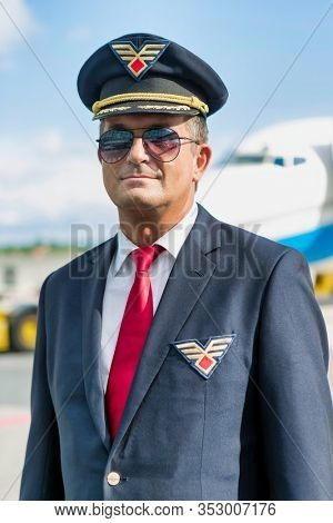 Portrait of mature pilot standing against airplane in airport