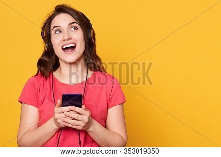 Close Up Portrait Of Happy Smiling Cute Woman Holding Smart Phones Isolated Over Yellow Background,