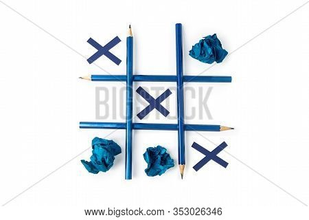 Tic Tac Toe Is Made Of Pencils And Paper. Blue Pencils On A White Isolated Background. Crosses From
