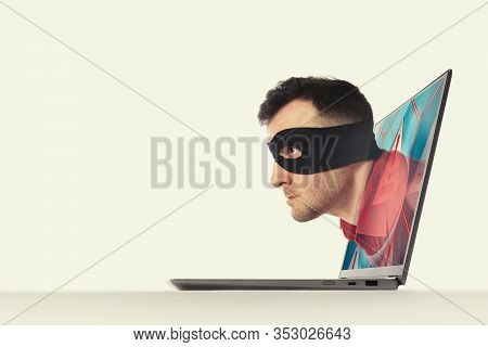 The Human In A Black Mask Moves Through Screen Of A Laptop.  Concept Of Hacking And Identity Theft.