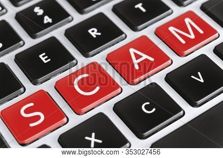Internet And Online Frauds And Scams Concept. Scam Word On Computer Keyboard.
