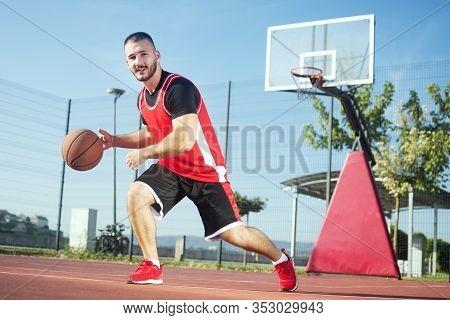 The Young Basketball Player Is Playing Basketball Or Streetbasket Outdoors On Playing Field.