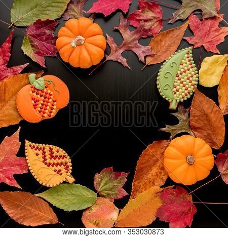 Autumn Leaves, Pumpkins  And  Homemade  Cookies On Wooden Table With Copy Space.