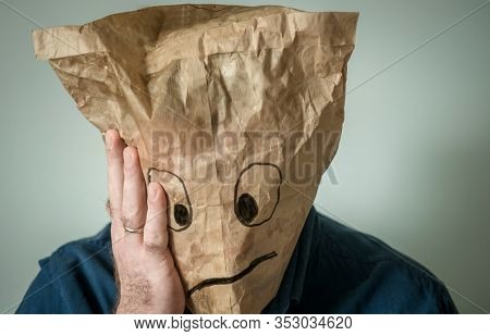Sad painted face. Lonely man with a paper bag on his head