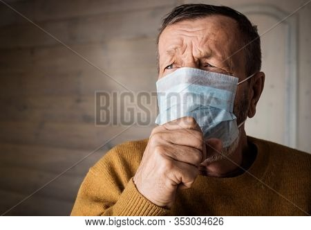 Elderly man in medical mask coughs indoors at home