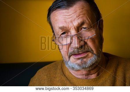 Pensive elderly wrinkled bearded man close-up face indoors