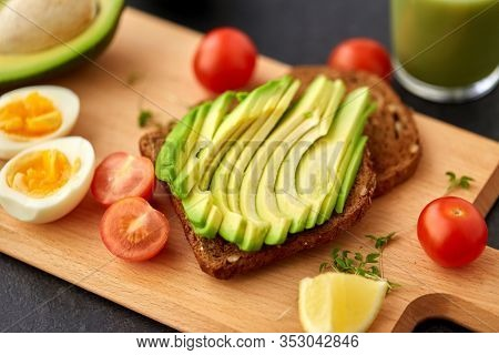food, eating and breakfast concept - toast bread with sliced avocado, eggs and cherry tomatoes on wooden cutting board